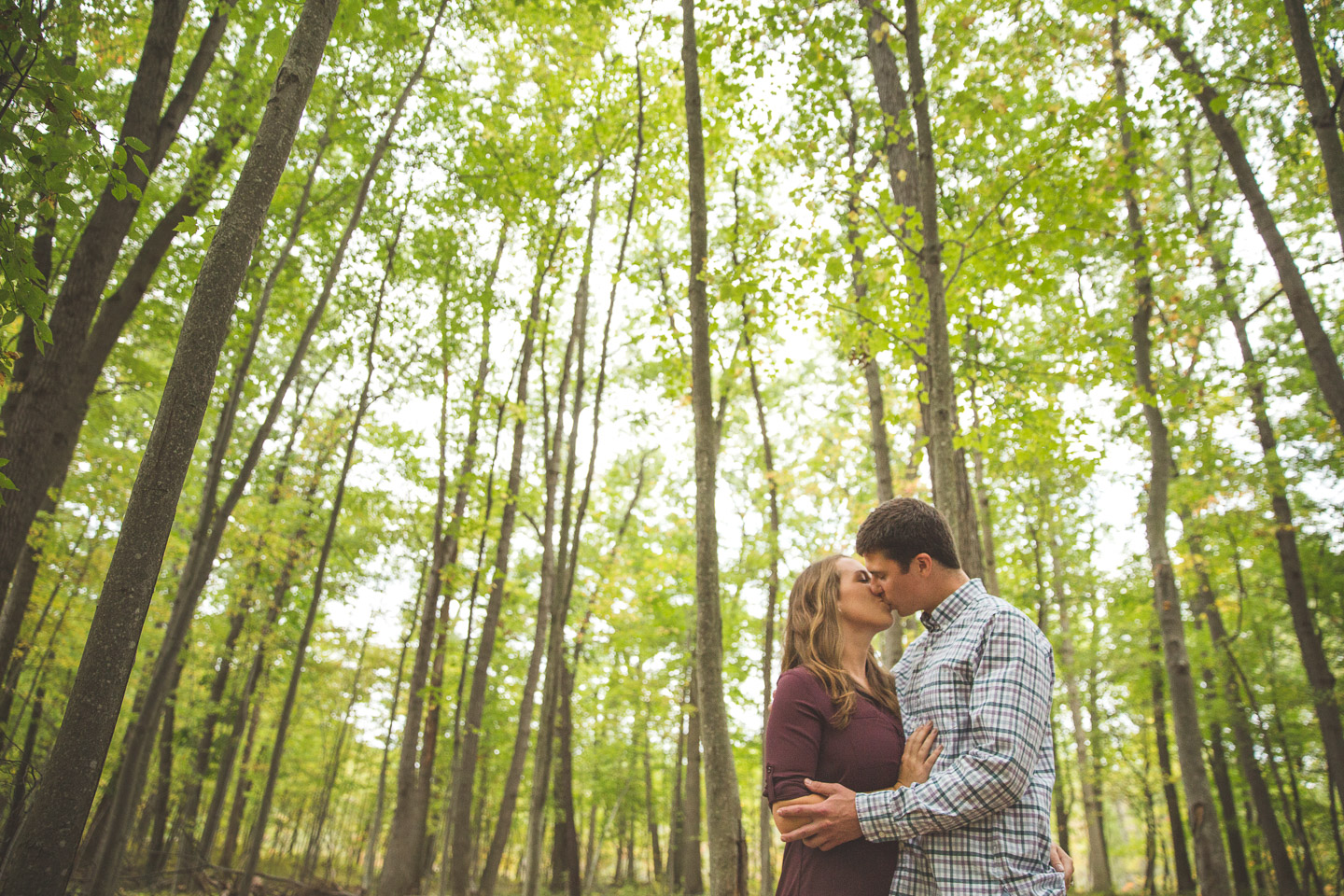 Engagement-Milford-Kensington-Metropark-Forest-Wide-Angle-Couple-Kissing