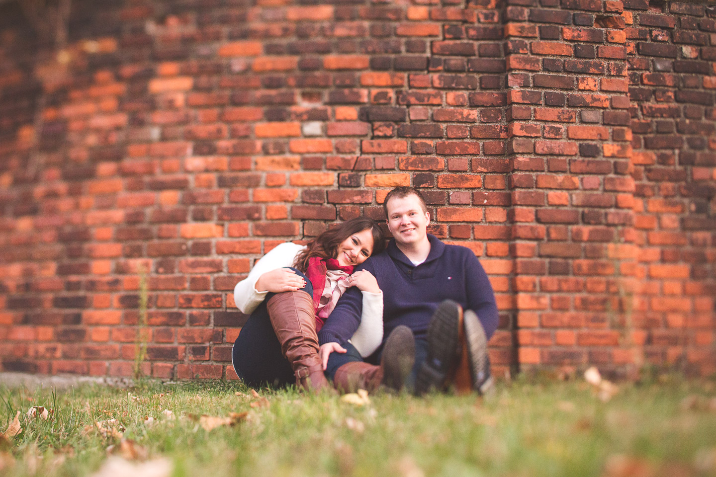 Engagement-Belle-Isle-Detroit-Couple-Sitting-Grass-Brick-Wall